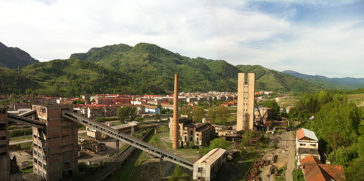 Imaginea panoramica  Vedere din Puțul central spre oraș (clădirile minei surpinse în imagine: stația unghiulară, compresoarele vechi, puțul vechi, ateliere, magazii)