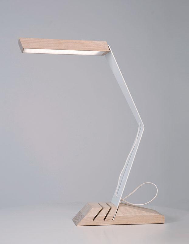 Lampa de birou N, design: Rizi  Designul lămpii este inspirat de misiunea proiectului casei solare EFdeN: o casă a viitorului, eficientă energetic și multifuncțională. Conceptul lămpii pornește de la stilizarea arhitecturală a formei clasice a lămpii de birou. Este realizată din lemn de fag, metal și asigură un iluminat sustenabil prin matricea de led folosită. Unghiul la care lumina cade pe suprafața orizontală poate fi ajustat prin mutarea piciorului în făgașul potrivit din baza de lemn. Dimensiuni: 550 mm x 420 mm x 100 mm