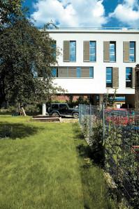 Fațada spre grădină a volumului finisat cu tencuială albă și aluminiu eloxat